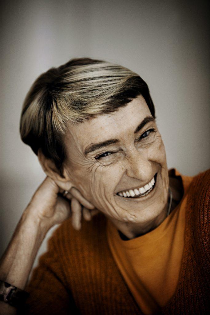 Gunilla Bergstöm leende med handen bakom örat som stöd.