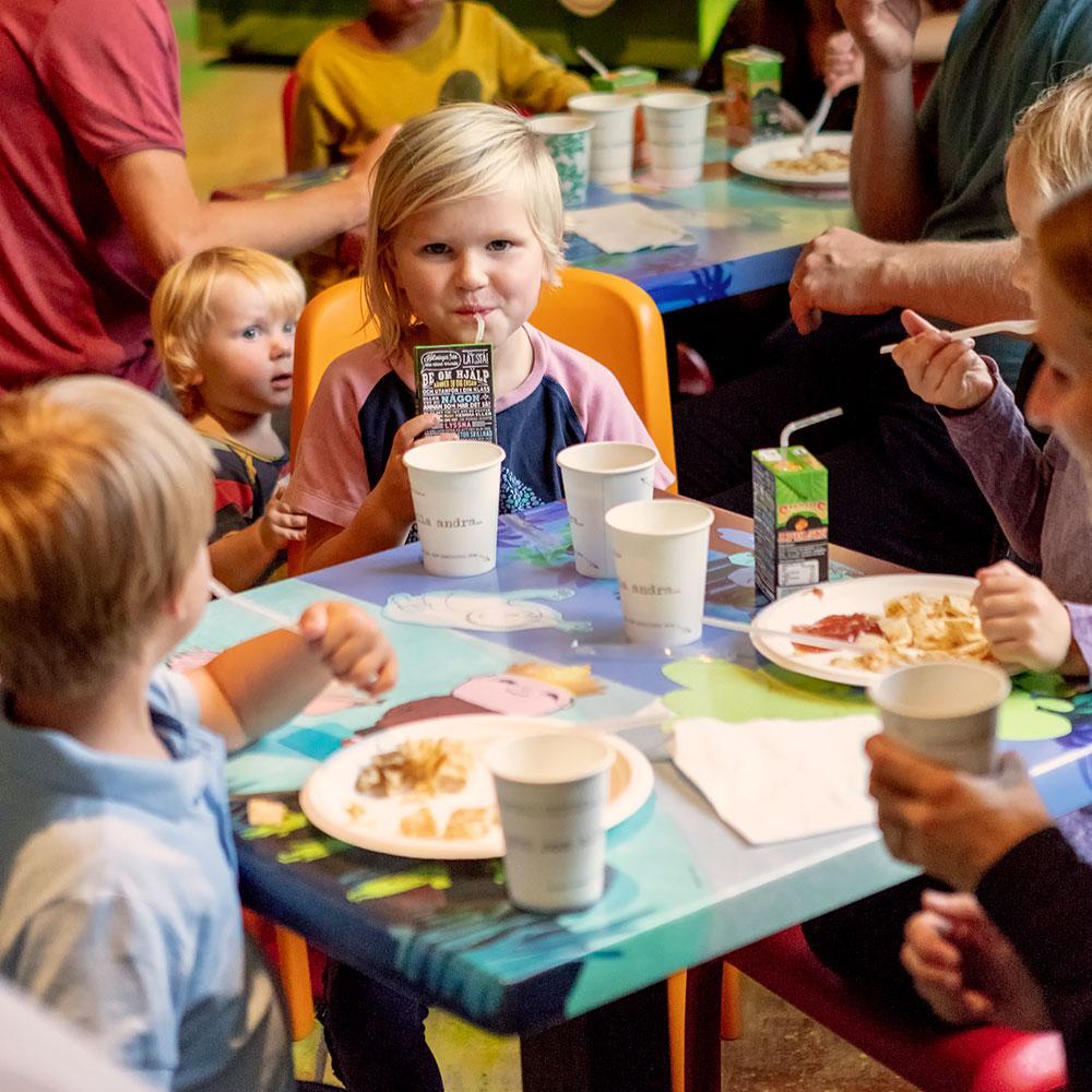 Barn som sitter runt ett bord och fikar i Mållgans kafé. Ett barn tittar fram bakom en orange stol.