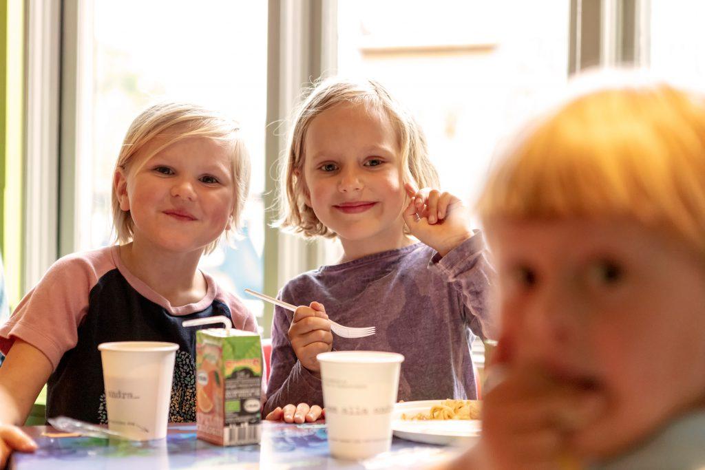 Tre barn som fikar. Ett barn håller en gaffel i handen. På bordet står en smakis med sugrör och två pappmuggar.