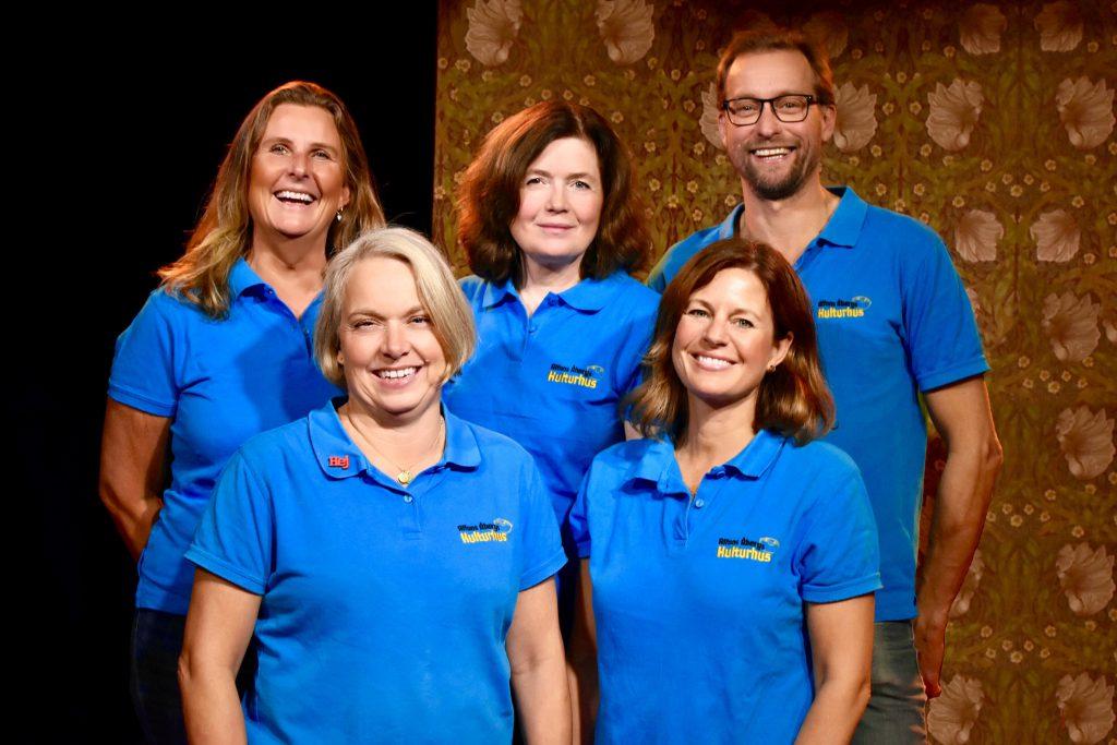 Gruppfoto från teatern på fem anställda vid Alfons Åbergs Kulturhus. De ser glada ut och samtliga har blå tröjor.